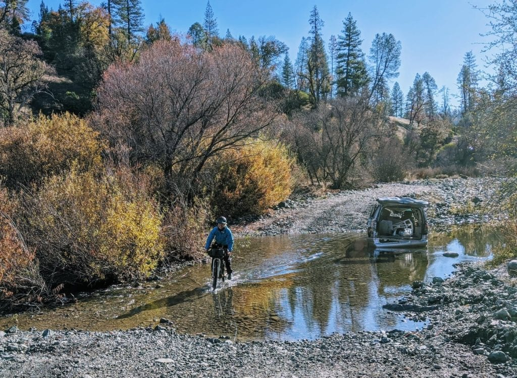 Bikepacker crosses river where abandoned vehicle is stuck