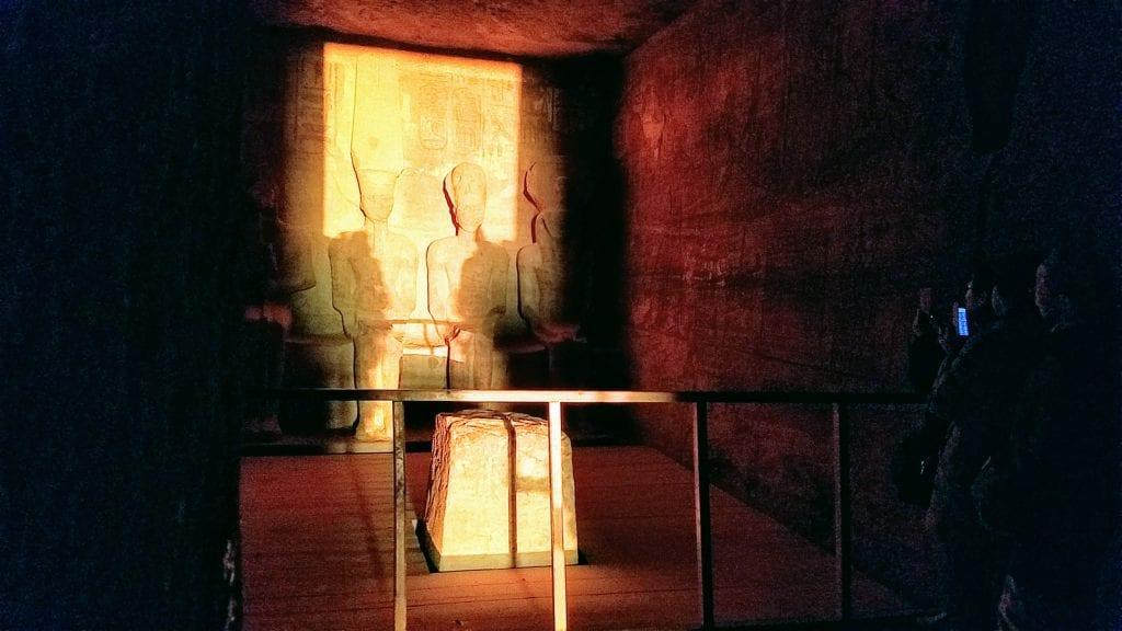 Sunlight shines on figures inside Abu Simbel sanctuary