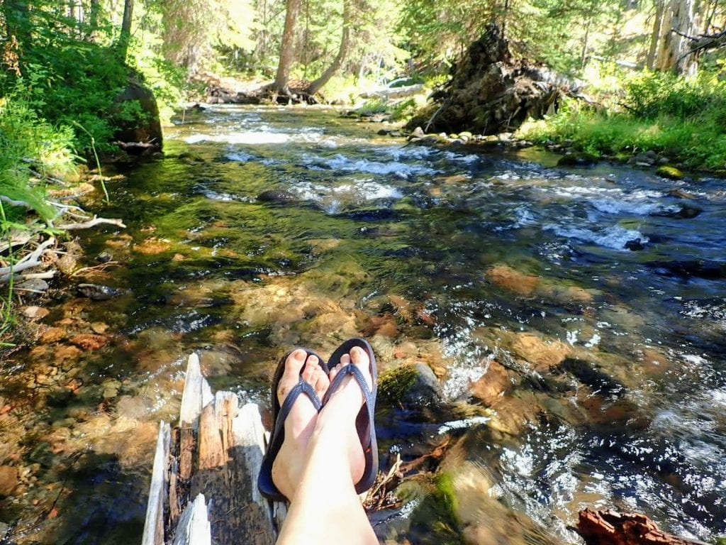 Feet in sandals on a log by a river