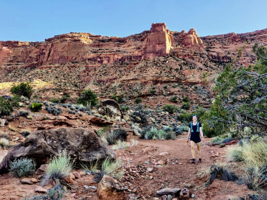Woman walks down wash in red rock canyon