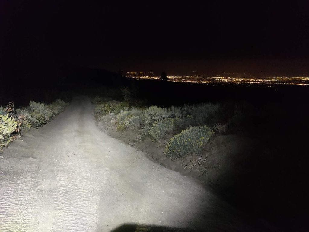 Bike light illuminates dirt road with lights of Boise in the distance